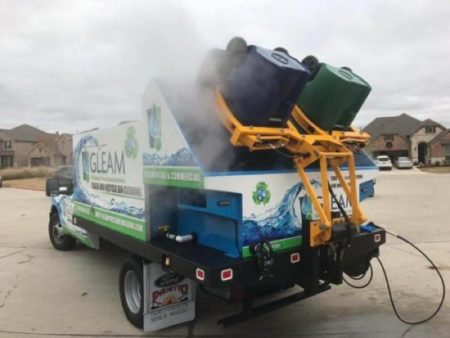 A GLEAM Truck cleans a pair of trash cans