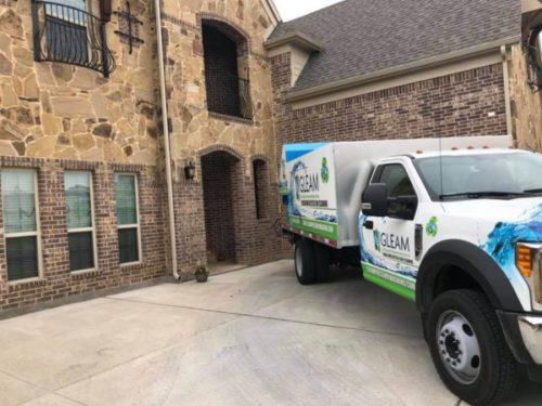 A GLEAM truck operator prepares to pressure wash a driveway