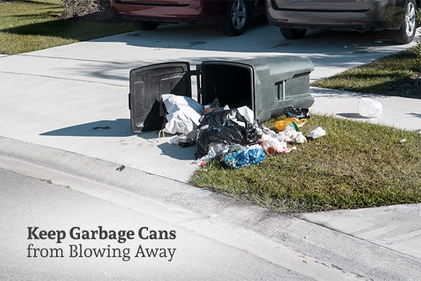 Garbage cans have been blown over and there is trash all over the driveway and yard, with the words, keep garbage cans from blowing away.